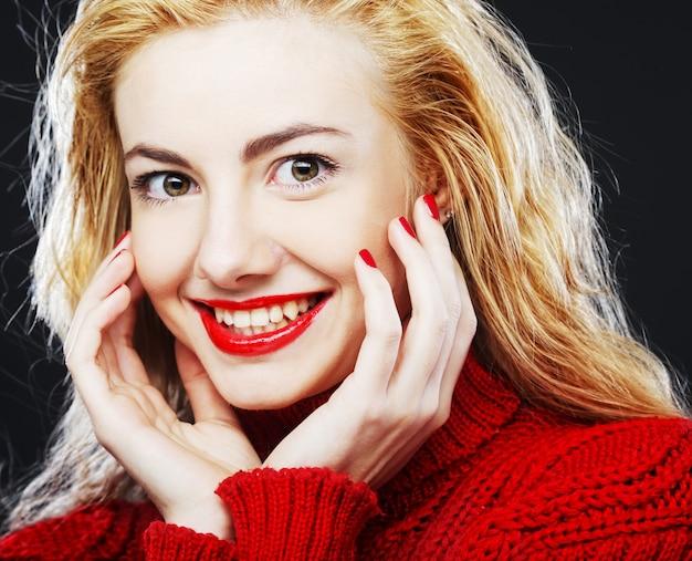 Portrait de charmante blonde souriante en pull rouge