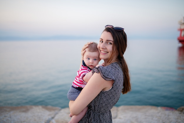 Portrait de charmante brune tenant son adorable fils de 6 mois en se tenant debout sur la plage au coucher du soleil.