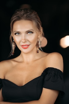 Le portrait d'une charmante dame caucasienne pose pour l'appareil photo, photo isolée sur fond sombre flou