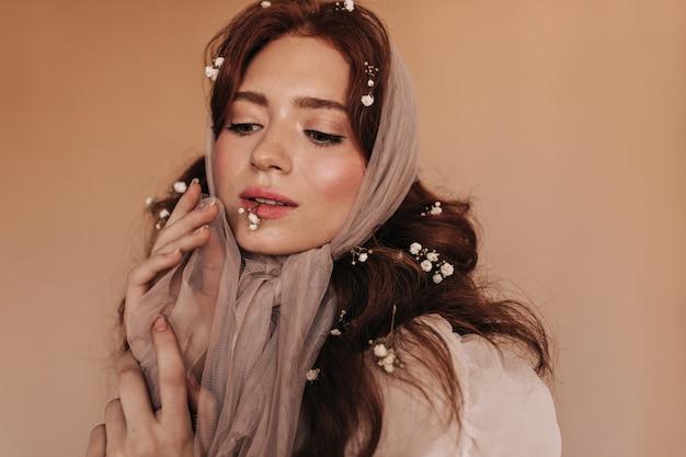 Portrait de charmante dame en foulard léger tenant une petite fleur dans la bouche sur fond beige.