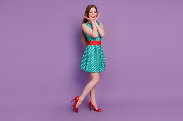 Portrait de charmante dame mignonne rêveuse posant porter une mini robe à talons hauts sur fond violet