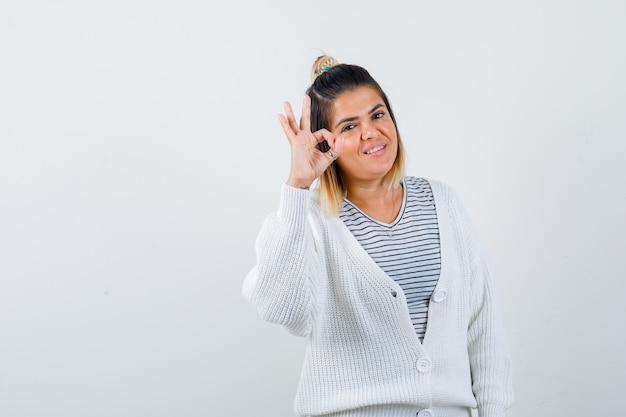 Portrait d'une charmante dame montrant un geste correct en t-shirt, cardigan et l'air joyeux