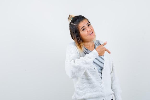 Portrait d'une charmante dame pointant vers le bas en t-shirt, cardigan et semblant fière
