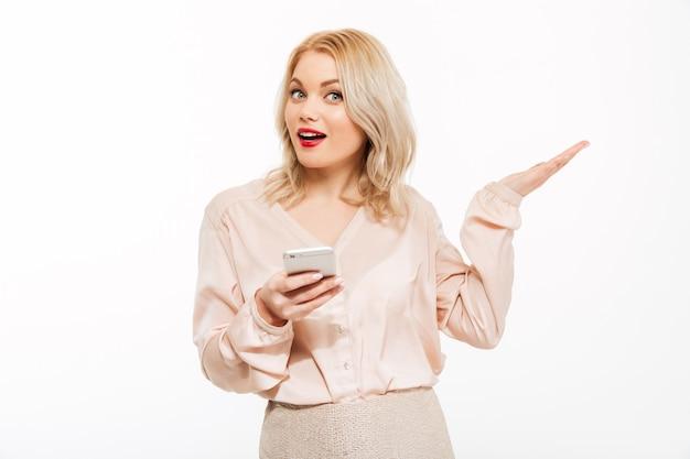 Portrait de charmante femme blonde tenant un smartphone et faisant un geste de la main de côté, isolé sur un espace papier peint blanc