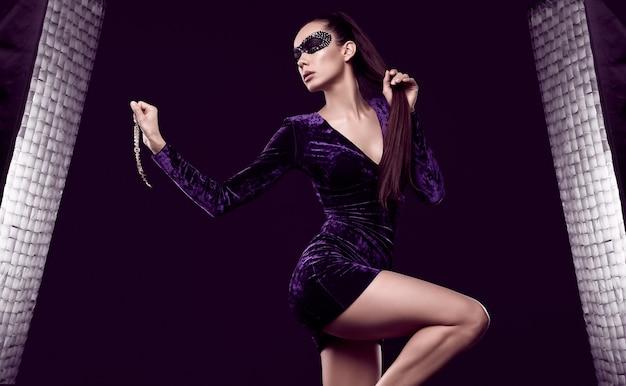 Portrait de charmante femme brune élégante en belle robe violette et masque de paillettes posant avec collier de diamants rouges sur fond noir en studio