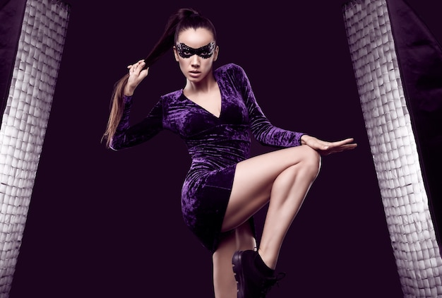 Portrait de charmante femme brune élégante en belle robe violette et masque de paillettes posant sur fond noir en studio