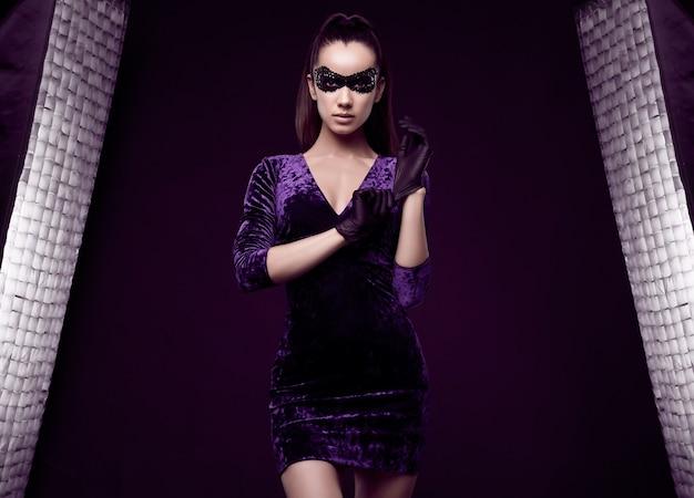 Portrait de charmante femme brune élégante en belle robe violette et masque de paillettes