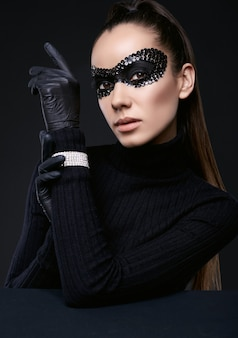 Portrait de charmante femme brune élégante en pull à col roulé et masque de paillettes posant sur fond noir en studio