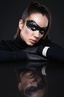 Portrait de charmante femme brune élégante en pull à col roulé noir et masque de paillettes posant sur une surface en miroir en studio
