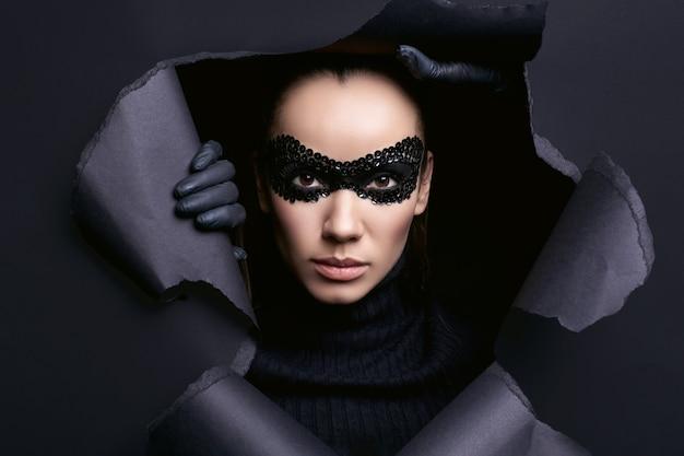 Portrait de charmante femme brune élégante en pull à col roulé noir et masque de paillettes regarde à travers un studio déchiré