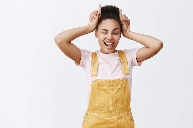 Portrait de charmante femme confiante à la peau sombre insouciante en salopette jaune, tenant l'index sur la tête, faisant des cornes et sortant la langue, étant têtue et rebelle