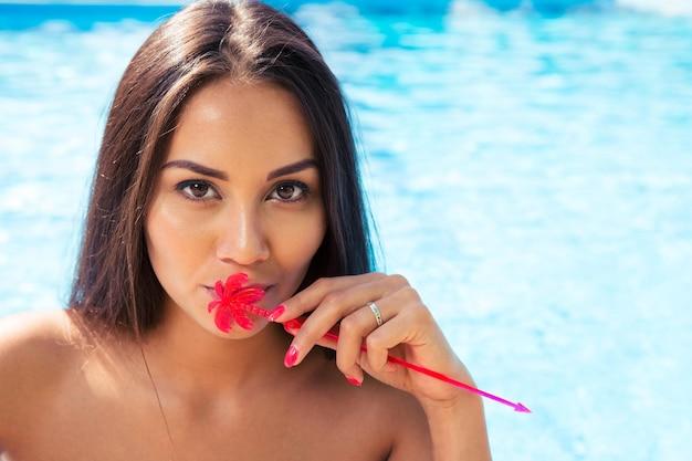 Portrait d'une charmante femme debout dans la piscine