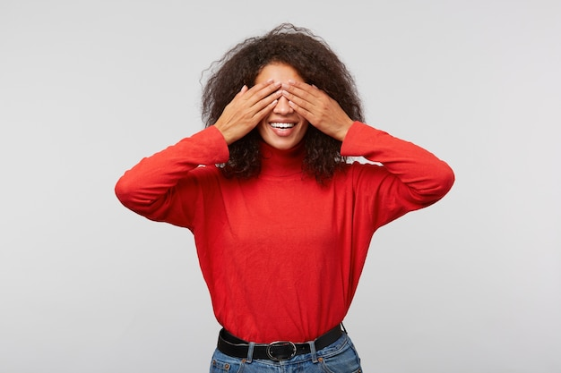 Portrait de charmante femme ludique avec une coiffure afro couvrant les yeux avec des paumes et souriant largement de joie