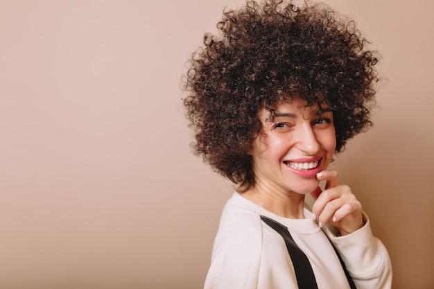 Portrait de charmante femme riant avec des boucles et un sourire merveilleux pose sur beige et tient une main près du visage