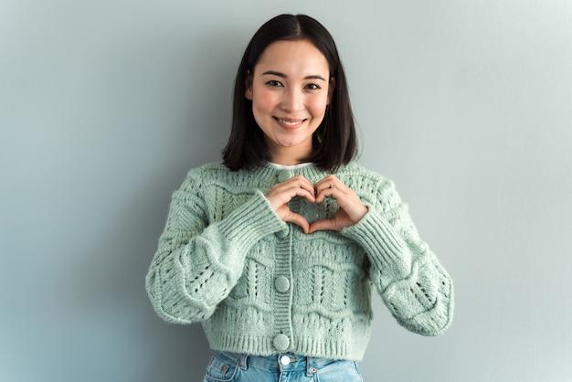 Portrait d'une charmante femme romantique et heureuse de jeune âge en forme de coeur avec les doigts, gesticulant le signe de charité de l'espoir d'amour, tout en regardant la caméra. prise de vue en studio intérieur