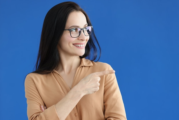 Portrait d'une charmante femme souriante montrant un geste de direction