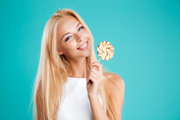 Portrait d'une charmante femme souriante tenant une sucette et regardant la caméra isolée sur fond bleu