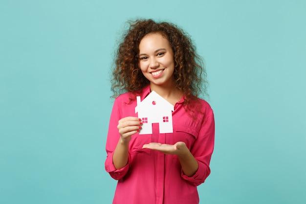 Portrait d'une charmante fille africaine dans des vêtements décontractés roses tenir dans la maison de papier à la main isolée sur fond de mur turquoise bleu en studio. concept de mode de vie des émotions sincères des gens. maquette de l'espace de copie.
