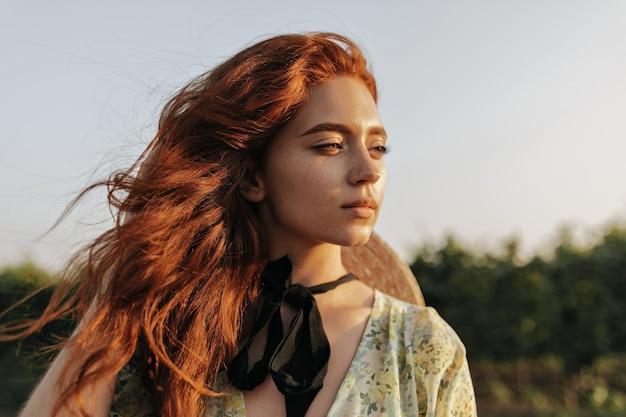 Portrait d'une charmante fille aux cheveux roux brillants, de belles taches de rousseur et un bandage sombre sur le cou en détournant les yeux et posant en plein air