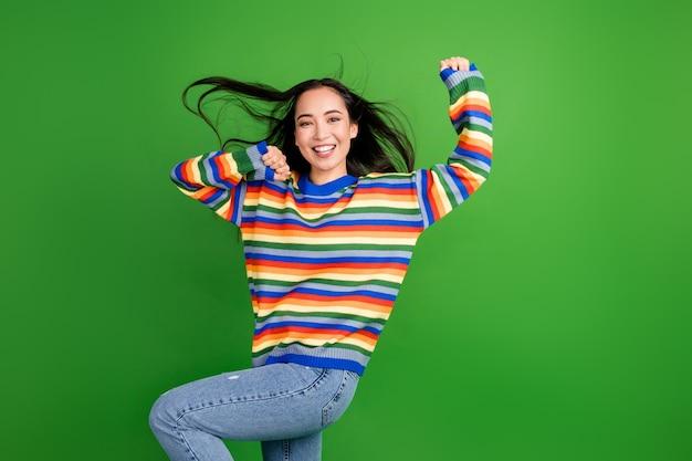 Portrait d'une charmante fille joyeuse dansant s'amusant à souffler de l'air isolé sur fond de couleur vert clair