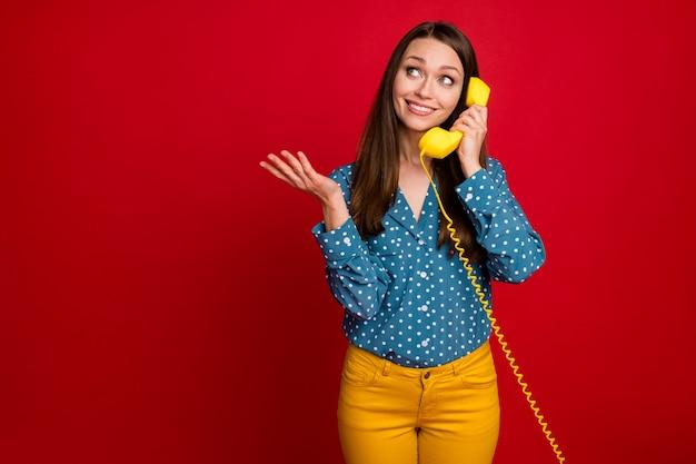 Portrait d'une charmante fille joyeuse et gaie à l'aide d'un récepteur appelant un ami isolé sur un fond de couleur rouge vif