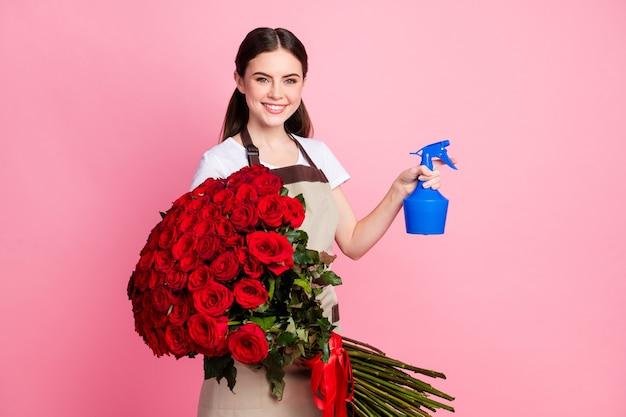 Portrait de charmante fille joyeuse tenant un grand bouquet de roses arrosant