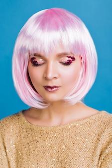 Portrait charmante jeune femme aux cheveux roses coupés, yeux fermés. maquillage attrayant, guirlandes roses sur les yeux, montrant de vraies émotions sensibles, femme magique, rêvant.