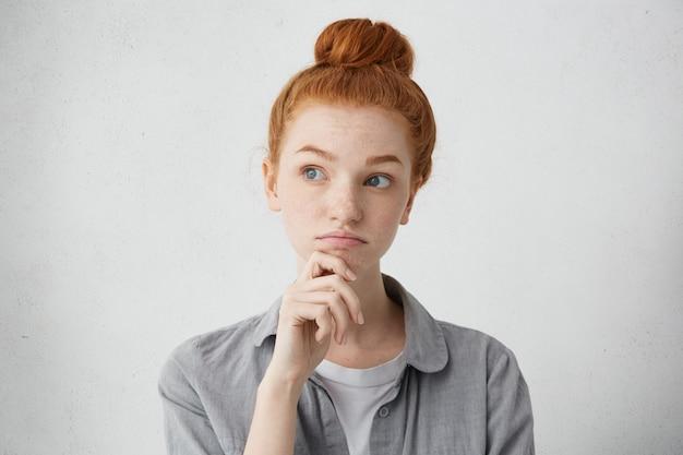 Portrait de charmante jeune femme aux cheveux rouges à la recherche de suite avec une expression douteuse, tenant la main sur son menton tout en réfléchissant à une proposition d'emploi intéressante et séduisante, pesant tous les avantages et inconvénients