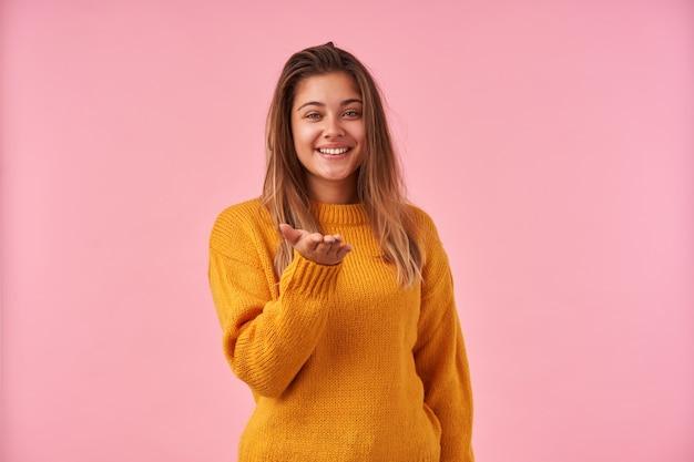 Portrait de charmante jeune femme brune à la recherche positive avec un sourire agréable, gardant sa paume levée en se tenant debout contre le rose