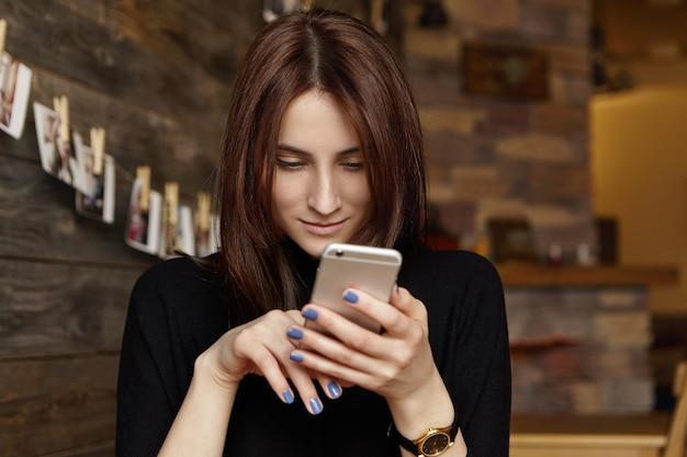 Portrait de charmante jeune femme européenne brune parcourant le fil d'actualité via les réseaux sociaux