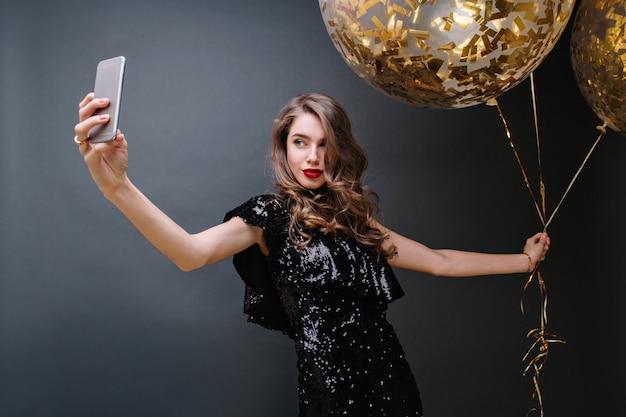 Portrait charmante jeune femme en robe de luxe noire, avec de longs cheveux bruns bouclés, des lèvres rouges prenant selfie avec de gros ballons pleins de guirlandes dorées. magnifique modèle, célébration.