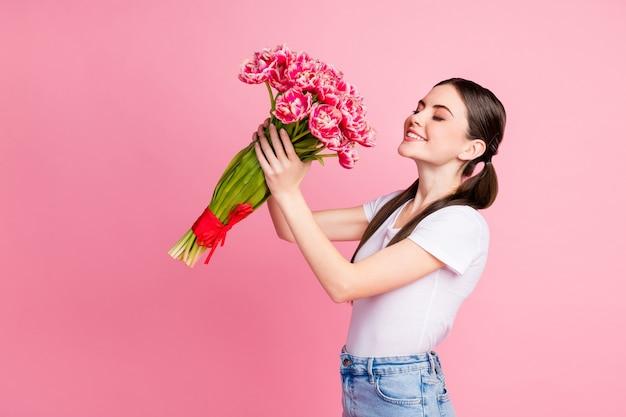 Portrait de charmante jeune fille tenant dans les mains bouquet de fleurs romantiques