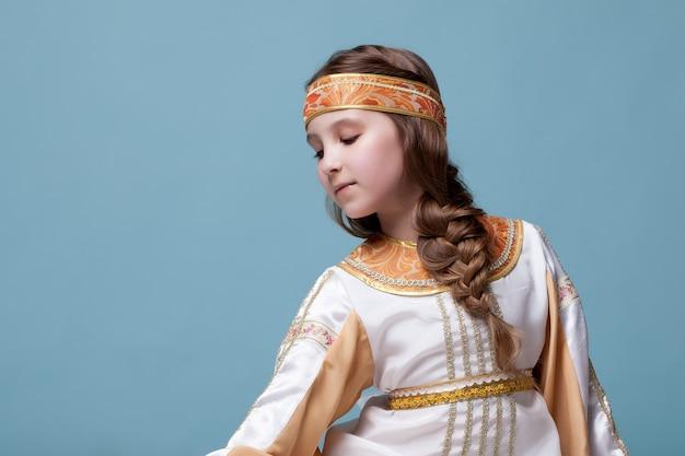 Portrait de charmante petite danseuse folk posant sur fond bleu