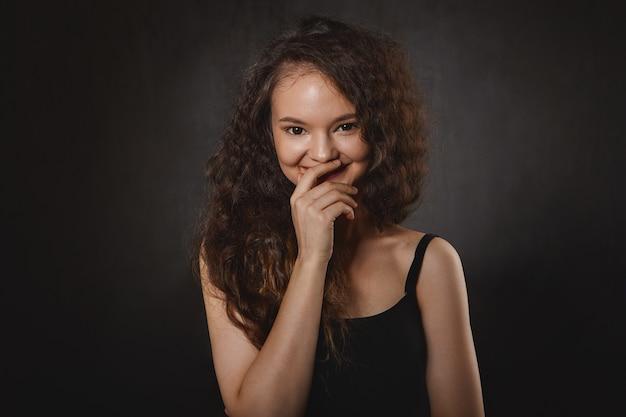 Portrait de charmante sorcière aux yeux noirs et cheveux noirs lâches touchant les lèvres et souriant mystérieusement, ayant des pouvoirs psychiques. belle femme brune astrologue en riant