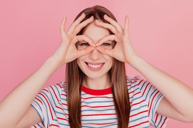 Portrait de charmantes douces doigts de dame funky montrent la forme de jumelles de signe okey sur fond rose