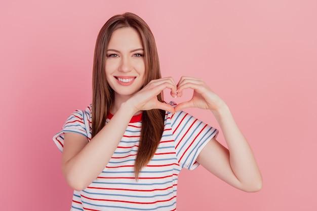 Portrait de charmants doigts de dame assez mignons montrent le signe du coeur sourire rayonnant à pleines dents sur fond rose