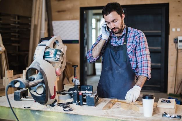 Portrait de charpentier appelant par téléphone intelligent à l'atelier