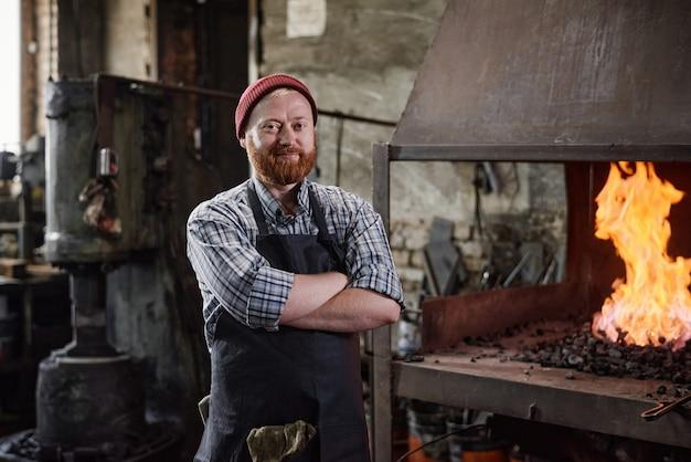Portrait de charpentier barbu mature debout avec les bras croisés et regardant la caméra travaillant dans l'atelier