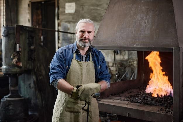 Portrait de charpentier mature en tablier regardant la caméra debout près du four dans l'usine