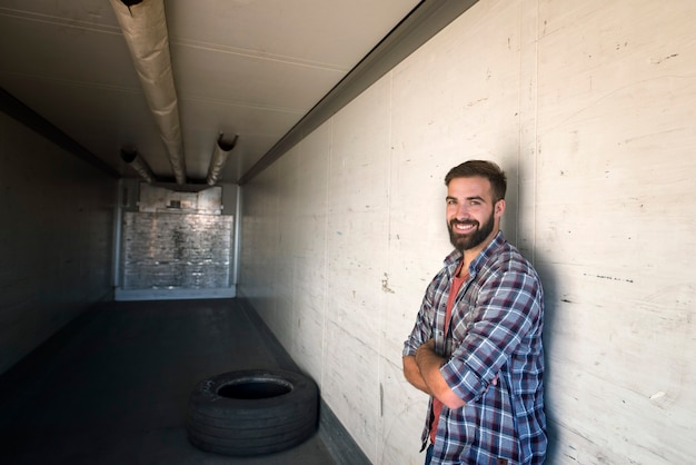 Portrait de chauffeur de camion avec les bras croisés debout dans une remorque de camion vide