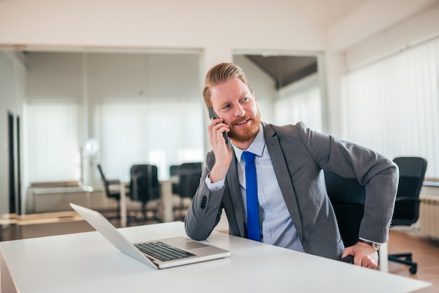 Portrait d'un chef d'entreprise parlant au téléphone au travail.