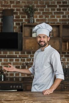 Portrait de chef masculin debout dans la cuisine présentant