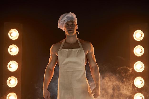 Portrait de chef musclé portant tablier blanc et chapeau de fromage, posant sur fond fumé femme au foyer masculine. mari dans la cuisine. boucher brutal.