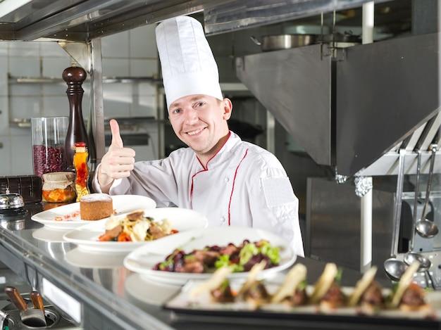 Portrait d'un chef avec des plats cuisinés dans la cuisine du restaurant.