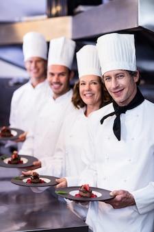 Portrait de chefs heureux présentant leurs assiettes à dessert