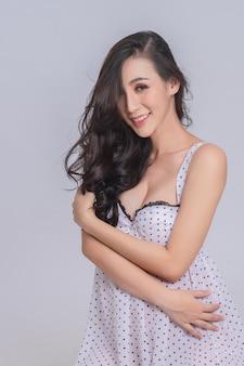 Portrait de cheveux longs beau modèle vêtu d'une robe à pois sur fond gris.