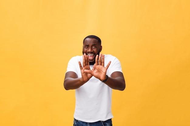Portrait choqué et contrarié, jeune homme levant les mains pour dire non, arrêt, isolé, orange, fond