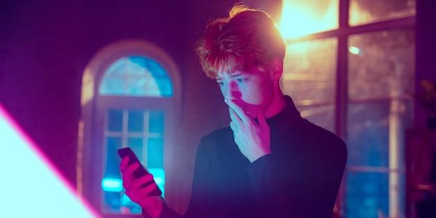 Portrait cinématographique d'un beau jeune homme dans un intérieur éclairé au néon