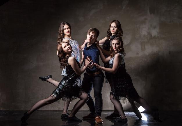 Portrait De Cinq Danseurs, Quatre Filles Entourant Le Gars Sur Fond Sombre Photo Premium