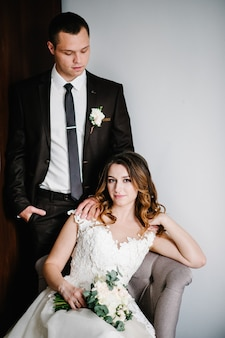 Portrait classique de la mariée et le marié à la maison dans le contexte de la pièce. bonne journée jeune couple. le concept des vacances et de l'amour dans la famille. vacances de mariage.